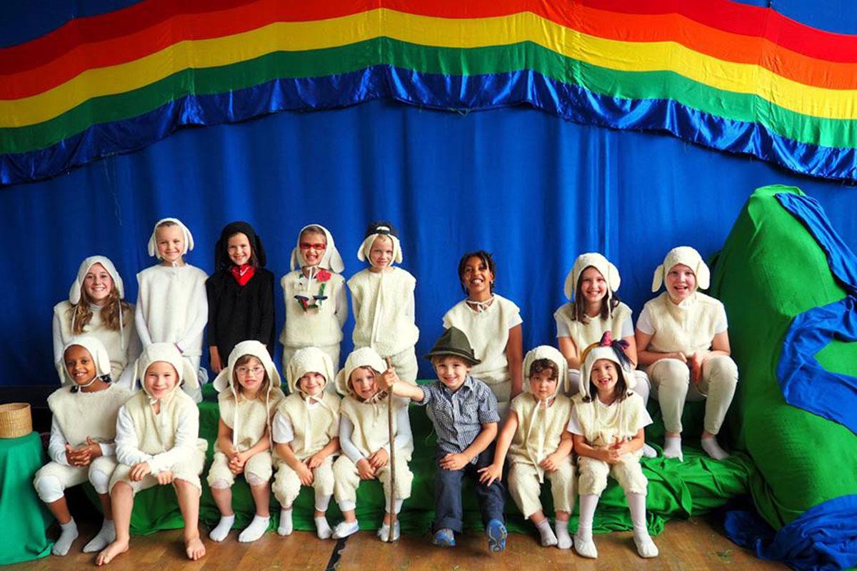 Eine Gruppe von Kinder unter einem Regenbogen.