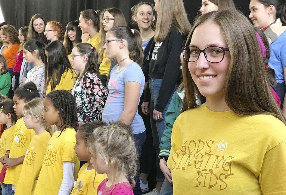 Mädchen mit Brille lächelt in die Kamera, im Hintergrund KISIs