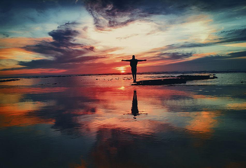 Foto zeigt Sonnenuntergang mit Person, die ihre Arme ausstreckt