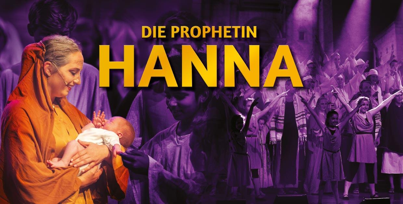 Frau, die Prophetin Hanna, hält ein Baby im Arm. Im Hindergrund ist ein ein Kinder- und Jugendchor zu sehen.